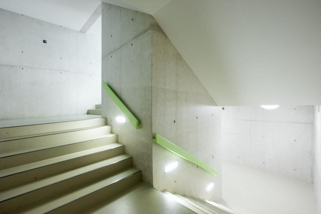 Zurückhaltende Materialisierung mit sanfter Farbgebung im Treppenhaus zur Turnhalle. Foto © René Rötheli, Baden