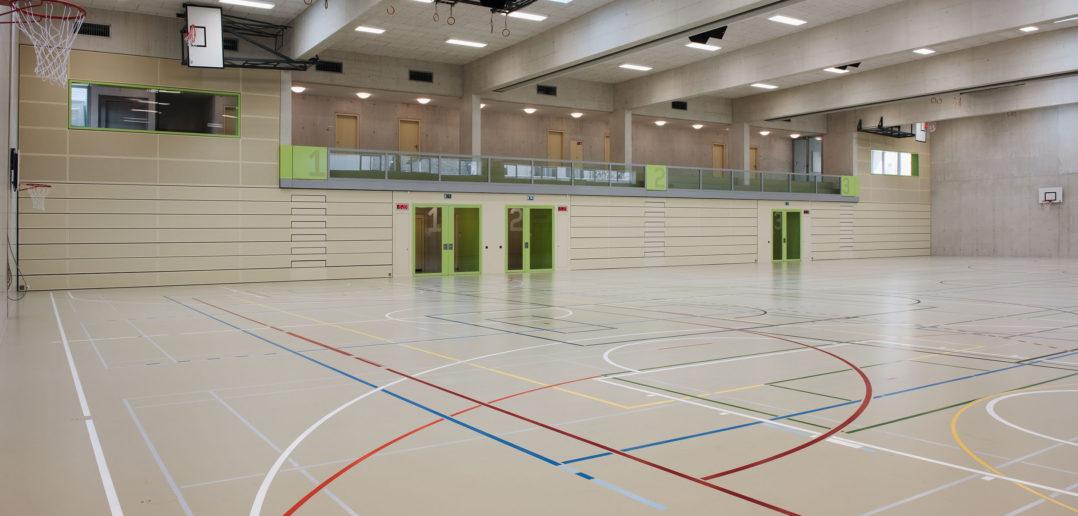 Der helle Beton und die Oblichter verleihen dem Inneren der Turnhalle eine leichte Erscheinung. Foto © René Rötheli, Baden