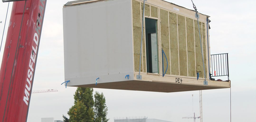 Mit Leichtigkeit hebt der Kran das Holz-Modul über das Breite-Quartier