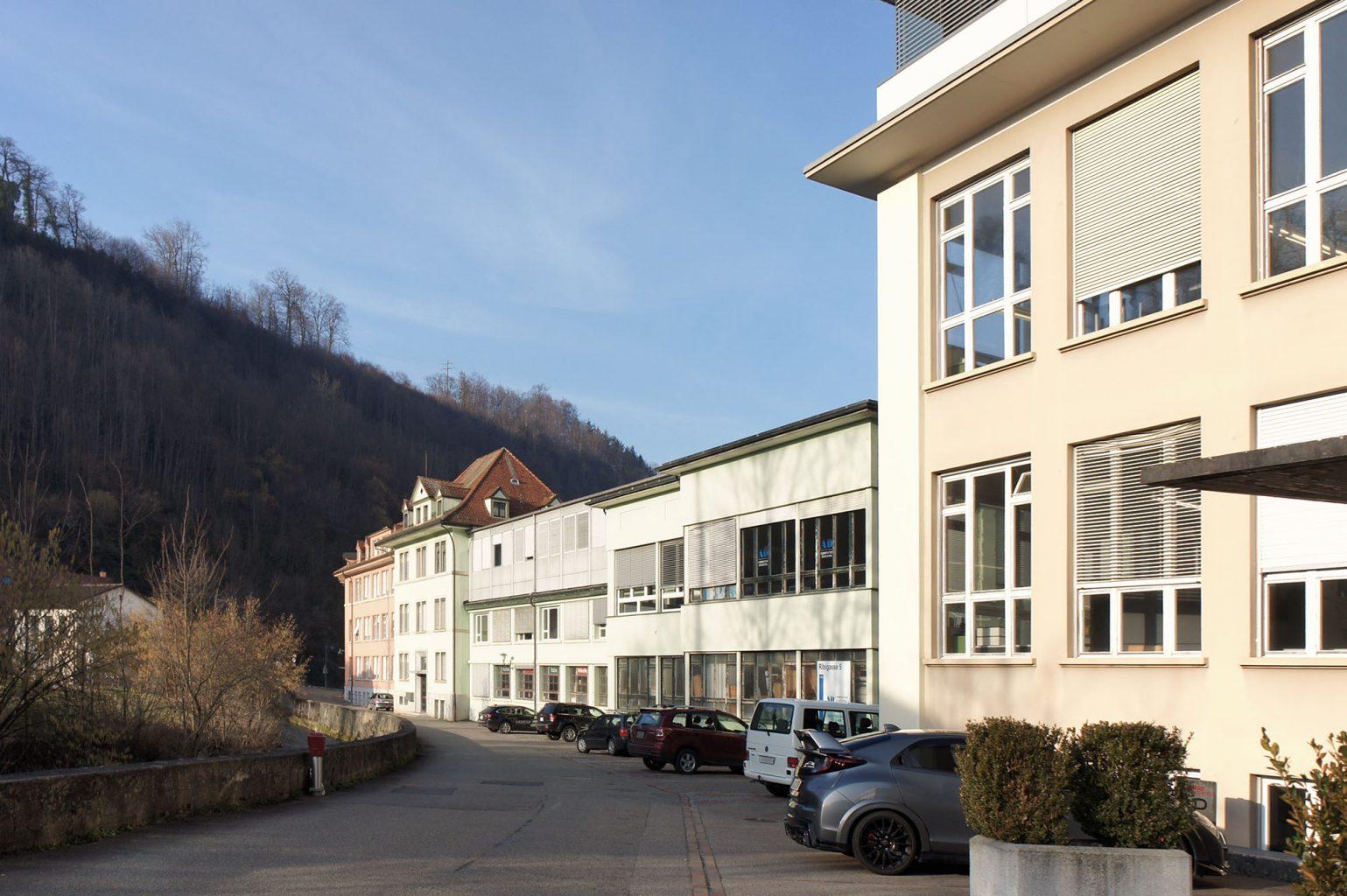 Gesamte Entwicklung: blassrosa (links), blassgrün (mitte), sandbraun (rechts), mit fragwürdigen Dachaufbauten in Metall, Hölstein © Architektur Basel