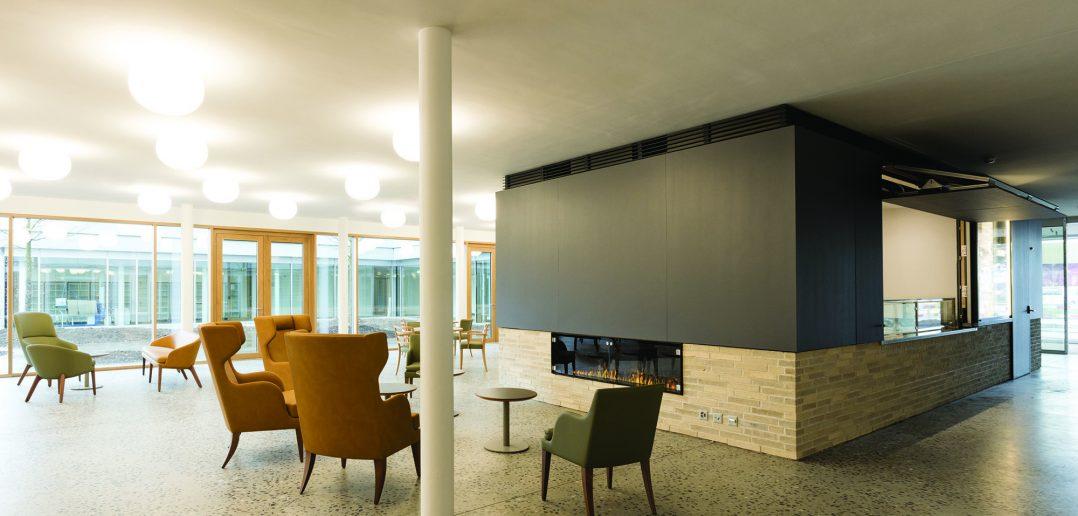 Neubau Pflegeheim Marthastift, Cafeteria im Erdgeschoss mit Effektfeuer, © Julian Salinas